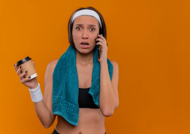 Young fitness woman in sportswear avec une serviette sur son cou tenant une tasse de café à la confusion tout en parlant au téléphone mobile debout sur un mur orange