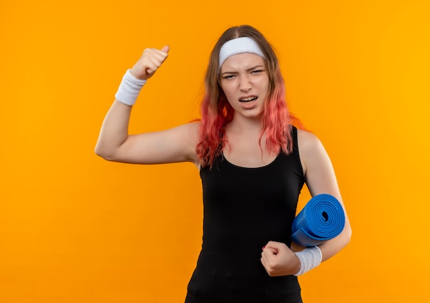 Young fitness woman in sportswear tenant un tapis de yoga levant le poing excité et heureux debout sur un mur orange