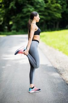 Young fitness woman runner stretching jambes avant de courir dans le parc