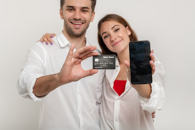 Young happy couple holding credit bank card using smartphone isolé sur fond blanc focus