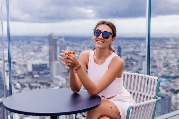 Young happy smiling caucasian woman traveller en robe ajustée et lunettes de soleil à l'étage élevé à bangkok femme élégante explorant une vue incroyable sur la grande ville