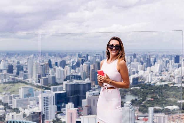 Young happy smiling caucasian woman traveller en robe de montage et lunettes de soleil à l'étage élevé à bangkok holding phone