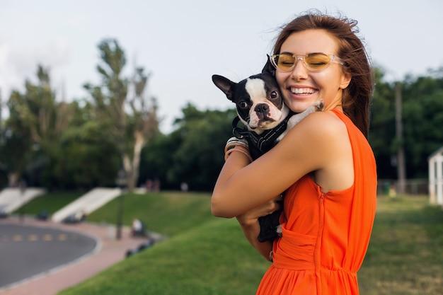 Young happy smiling woman holding boston terrier dog in park, journée ensoleillée d'été, bonne humeur, jouant avec animal de compagnie, câlins, vêtue d'une robe orange, lunettes de soleil, style d'été