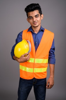Young indian man construction worker contre mur gris