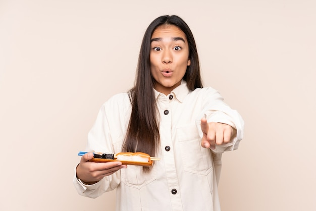 Young indian woman holding sushi isolé sur beige surpris et pointant vers l'avant