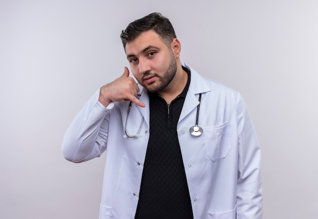 Young male doctor wearing white coat with stethoscopelooking confiant faisant appelez-moi geste