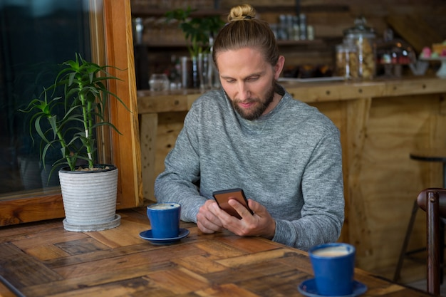 Young male hipster using mobile phone at table in coffee shop