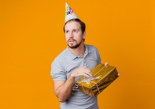 Young man in party cap holding gist fort à côté avec expression pensive debout sur un mur orange