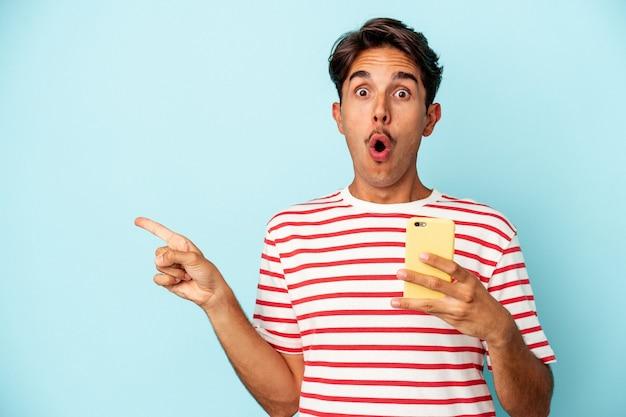 Young mixed race man holding mobile phone isolé sur fond bleu pointant vers le côté