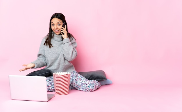 Young mixed race woman eating popcorn tout en regardant un film sur l'ordinateur portable en gardant une conversation avec le téléphone mobile avec quelqu'un