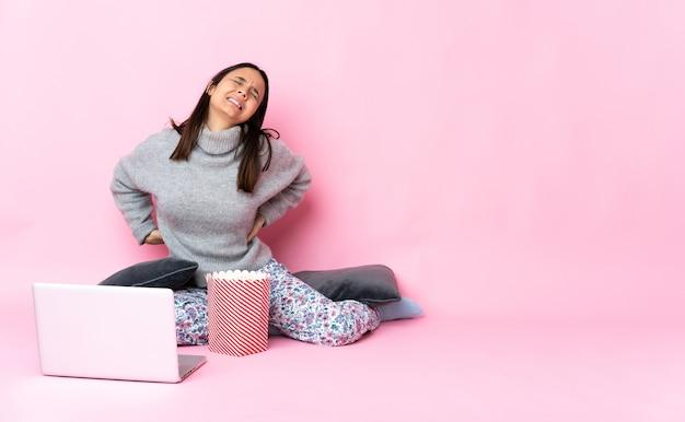 Young mixed race woman eating popcorn tout en regardant un film sur l'ordinateur portable souffrant de maux de dos pour avoir fait un effort