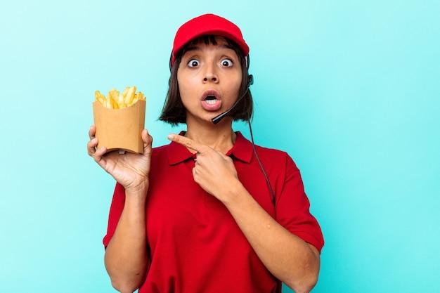 Young mixed race woman fast food restaurant worker holding frites isolé sur fond bleu pointant vers le côté