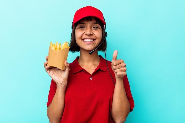 Young mixed race woman fast food restaurant worker holding frites isolé sur fond bleu souriant et levant le pouce vers le haut