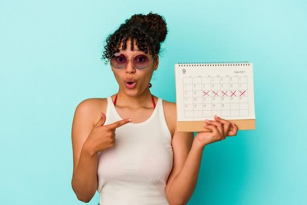 Young mixed race woman holding calendrier isolé sur fond bleu pointant vers le côté
