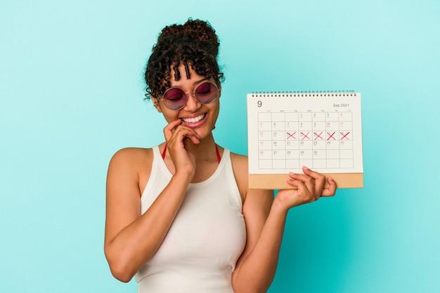 Young mixed race woman holding calendrier isolé sur mur bleu détendu penser à quelque chose en regardant un espace de copie.
