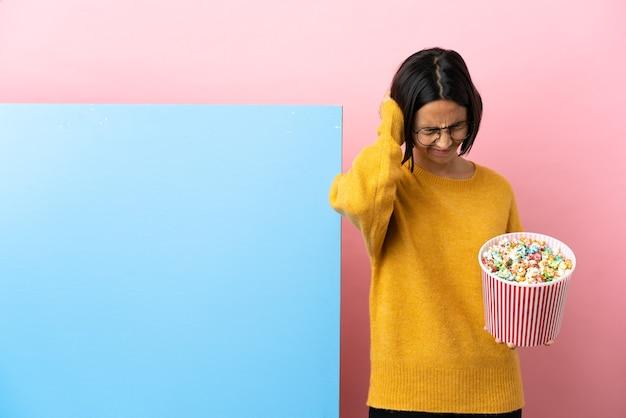 Young mixed race woman holding pop-corn avec une grande bannière sur fond isolé frustré et couvrant les oreilles