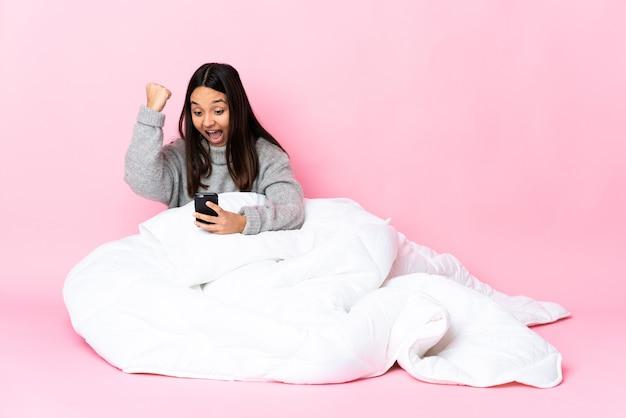 Young mixed race woman wearing pijama assis sur le sol avec téléphone en position de victoire