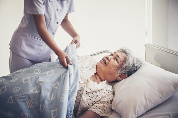 Young nurse prend soin des patients âgés lors de l'hospitalisation.