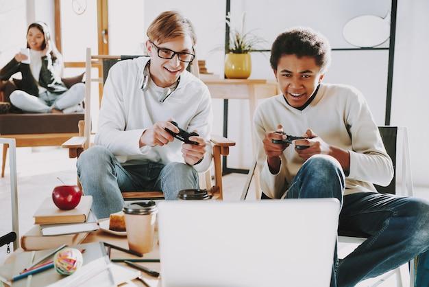 Young play dans le jeu de console vidéo sur ordinateur portable