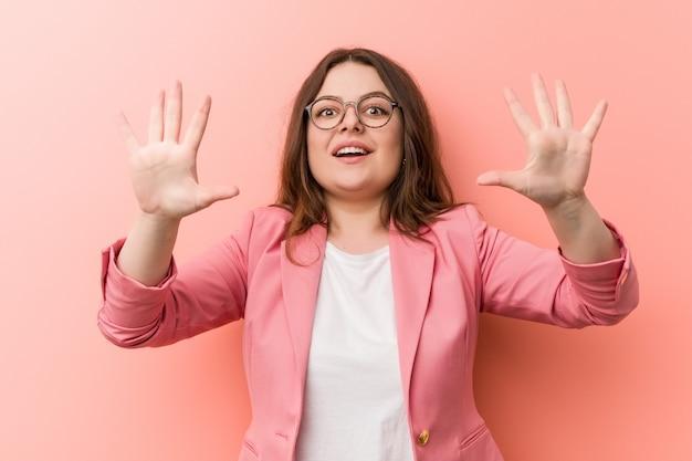 Young plus size business caucasian woman montrant le numéro dix avec les mains.
