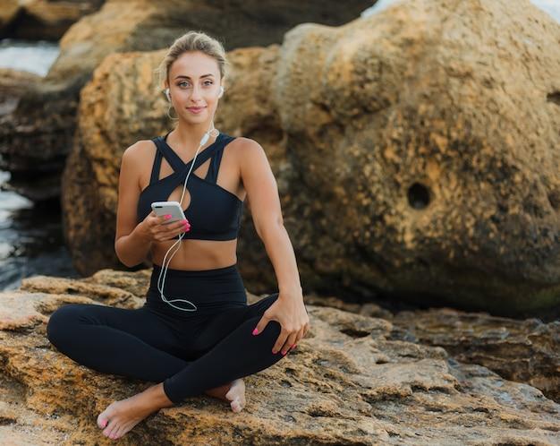 Young slim fit woman in sportwear écouter de la musique dans les écouteurs et à l'aide de smartphone tout en étant assis sur une pierre sur une plage sauvage