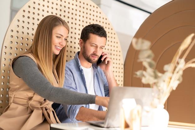 Young smiling businesswoman faisant une présentation à un collègue occupé avec smartphone tout en pointant sur l'écran du portable
