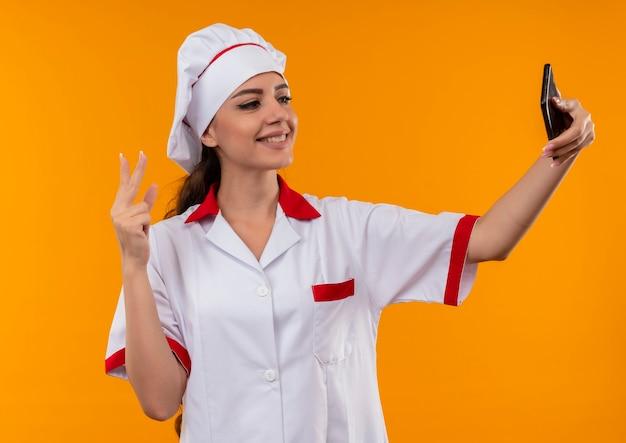 Young smiling caucasian cook girl en uniforme de chef regarde le téléphone et les gestes signe de la main de la victoire isolé sur le mur orange avec copie espace