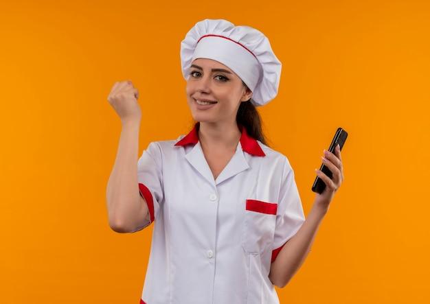 Young smiling caucasian cook girl en uniforme de chef tient le téléphone et lève le poing isolé sur un mur orange avec copie espace