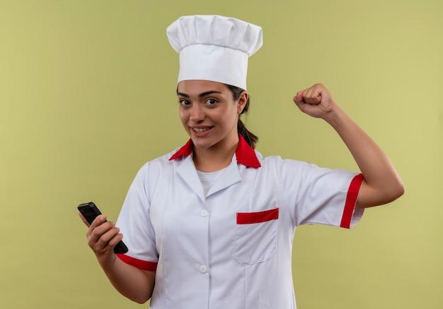Young smiling caucasian cook girl en uniforme de chef tient le téléphone et lève le poing isolé sur mur vert avec espace copie