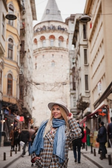 Young smiling caucasian woman in hat restant en face de la tour de galata