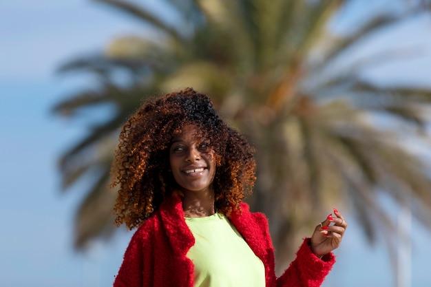 Young smiling curly fro woman standing outdoors tout en souriant et en détournant les yeux dans une journée ensoleillée