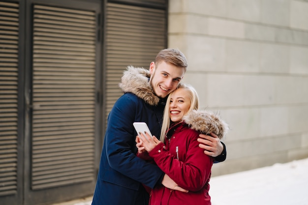 Young smiling happy european couple hugging in winter