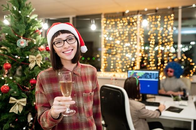 Young smiling office manager in santa cap holding flute of champagne en position debout par arbre de noël décoré