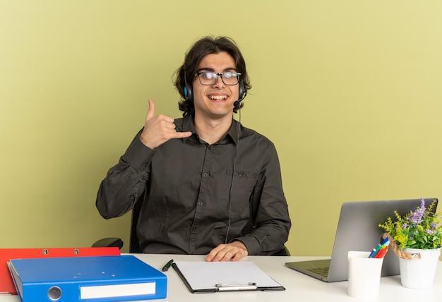 Young smiling office worker man sur les écouteurs dans des lunettes optiques se trouve au bureau avec des outils de bureau à l'aide de gestes d'ordinateur portable signe de main de téléphone