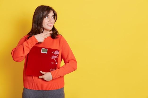 Young smiling woman holding floor scale et pointant de côté avec l'index, belle dame montrant quelque chose à l'espace vide, fille aux cheveux noirs démontrant ad,