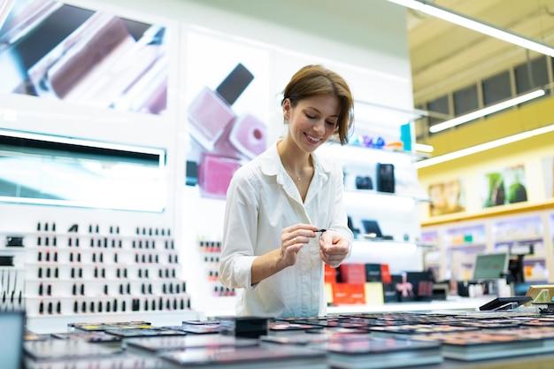 Young smiling woman in cosmetics shop teste les ombres à paupières avec aplicator