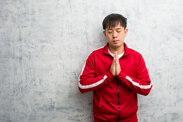 Young sport fitness chinois priant très heureux et confiant