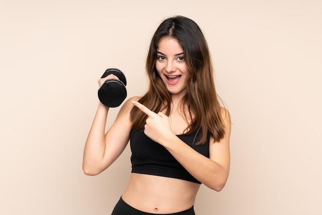 Young sport woman making haltérophilie sur mur beige, pointant le doigt sur le côté