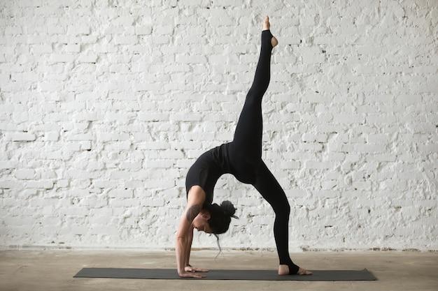 Young yogi attractive woman in bridge pose, loft backgroun blanc