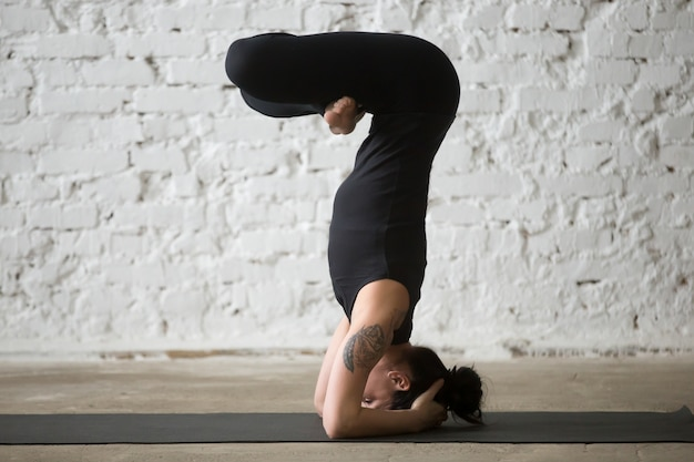 Young yogi attractive woman in headstand pose, white loft backgr