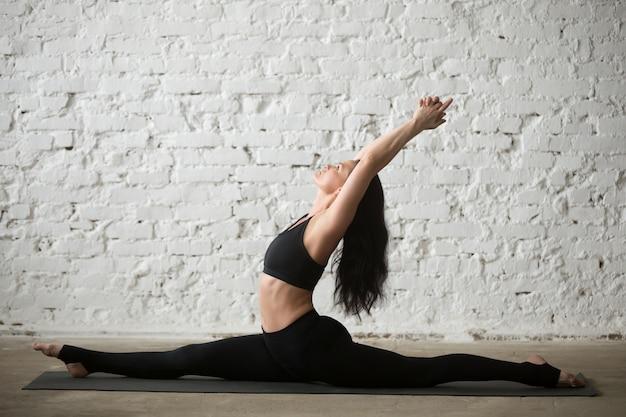 Young yogi attractive woman in monkey god pose, fond blanc