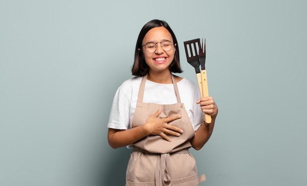 Yoyoung jolie womanung femme hispanique riant à haute voix à une blague hilarante, se sentir heureux et joyeux, s'amuser