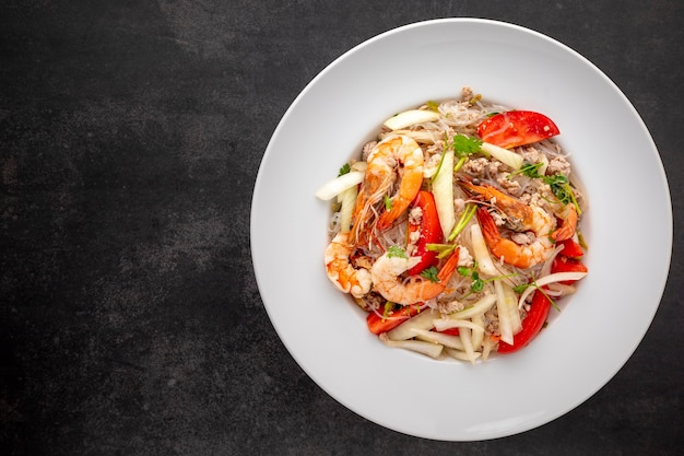 Yum woon sen, cuisine thaïlandaise, salade de nouilles en verre thaïlandais dans une assiette en céramique blanche sur fond de texture de ton sombre avec espace de copie pour le texte, vue de dessus