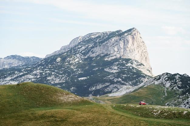 Zabljak monténégro juillet touristes dans une voiture rouge campé sur l'herbe dans le contexte d'un rocher