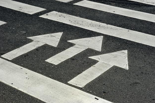 Zèbre piéton traversant la route - trois flèches indiquant le sens de la marche