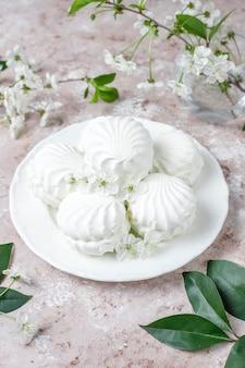 Zéphyr blanc, délicieuses guimauves avec des fleurs de printemps, vue de dessus