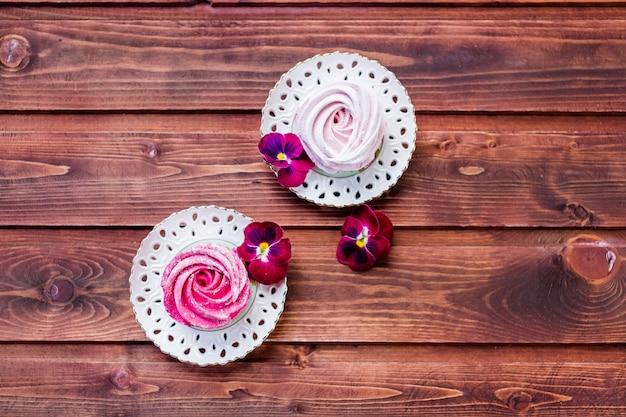 Zéphyr coloré sur fond en bois.ensemble de zéphyr ou de guimauve blanc et rose fait maison sur fond en bois. guimauve, meringue, zéphyr, pensée meringues savoureuses espace copie