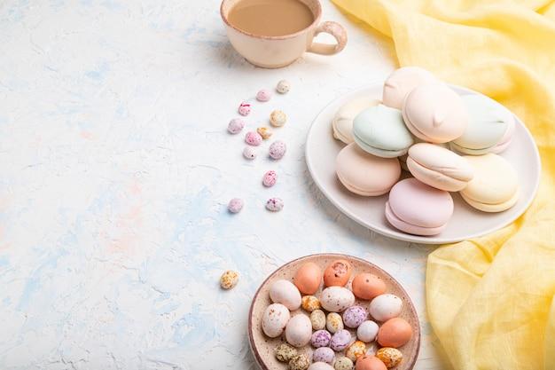 Zéphyr coloré ou guimauve avec une tasse de café et des dragées sur fond de béton blanc.