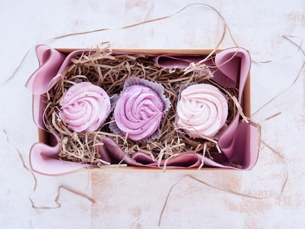 Zephyr fait maison en forme de fleurs roses. guimauves aux pommes avec purée de baies dans une boîte cadeau