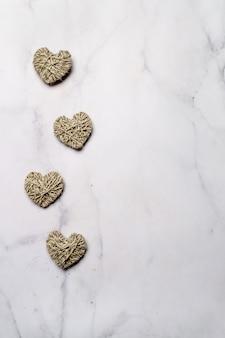 Zéro déchet, concept écologique de la saint-valentin. coeurs avec du fil sur fond de marbre blanc. copiez l'espace pour le texte ou le design. vue de dessus ou pose à plat verticale.